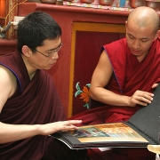 H.E. Tsem Tulku Rinpoche showing H.H. Zong Rinpoche pictures of his work